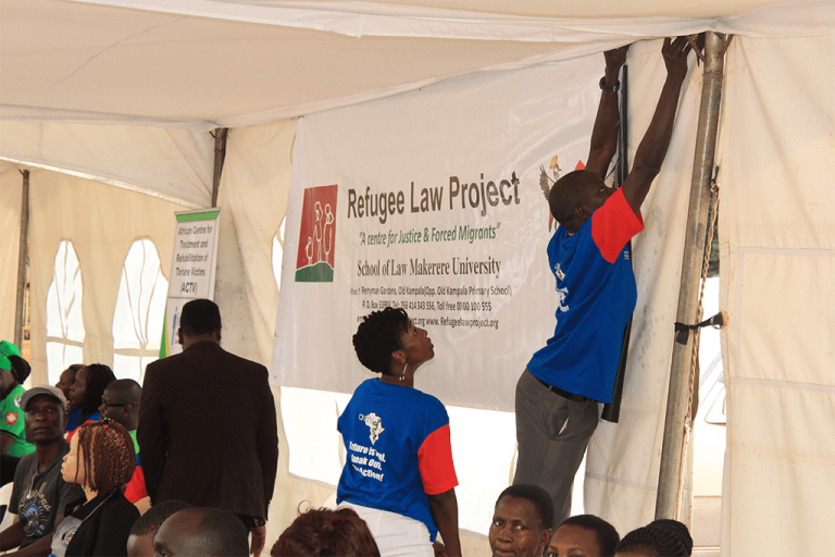 Refugee Law Project staff setting tent during the event